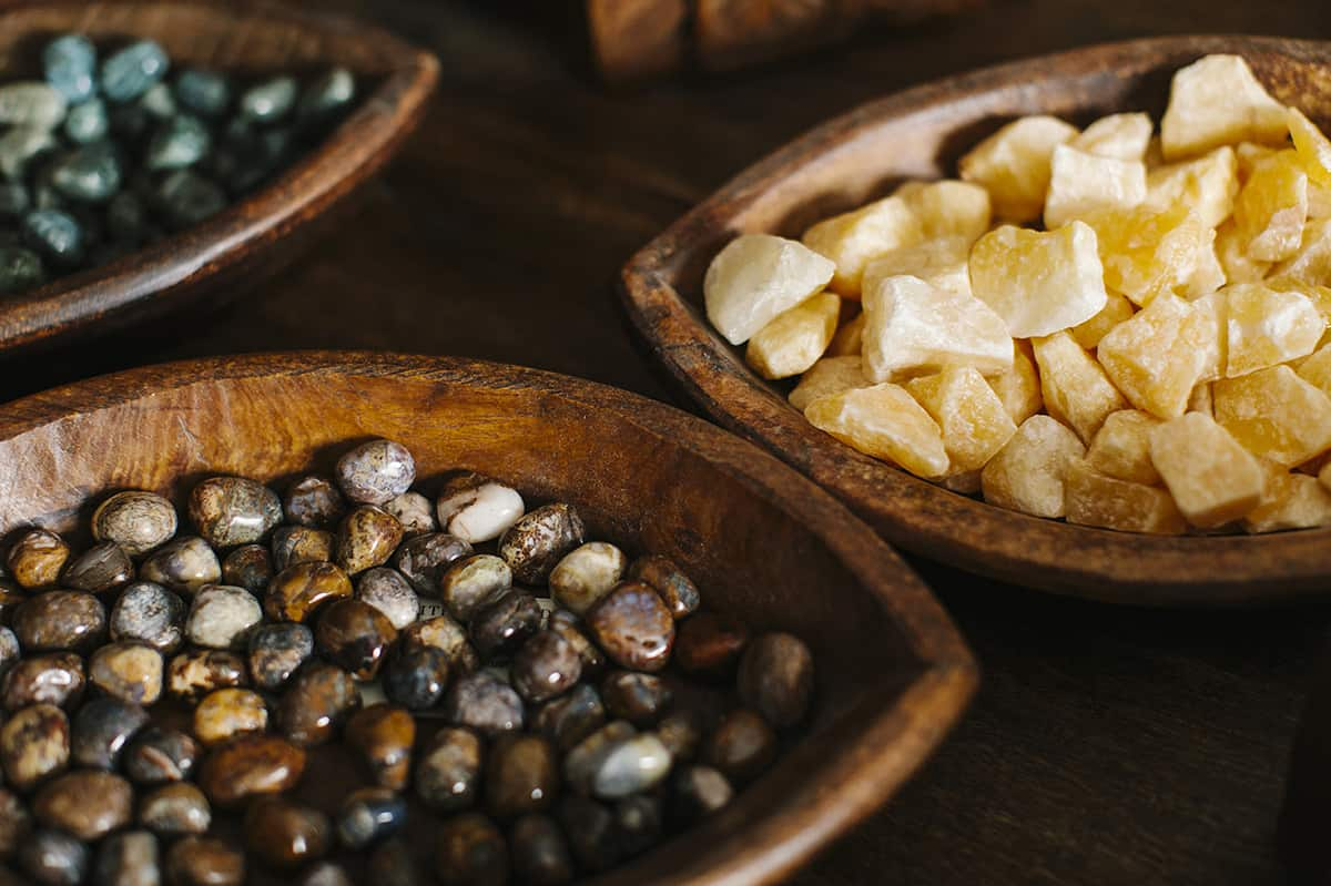 different kinds of healing stones in wooden bowls
